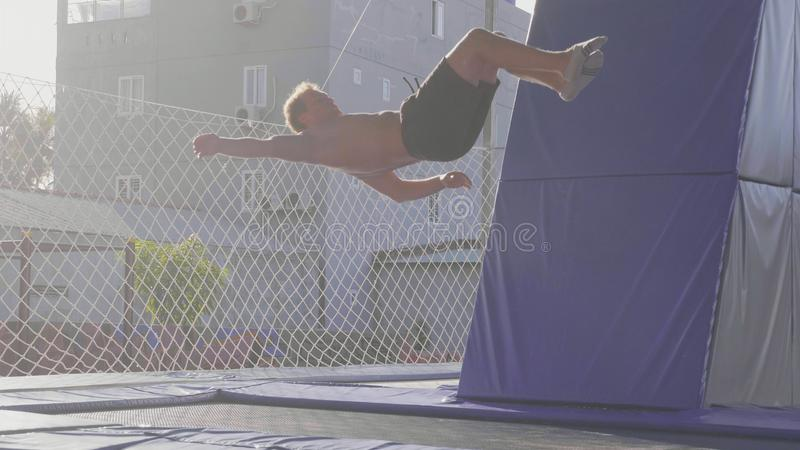 Yrkesmässig gymnastbanhoppning på trampolinen och göratrick i luft royaltyfria foton