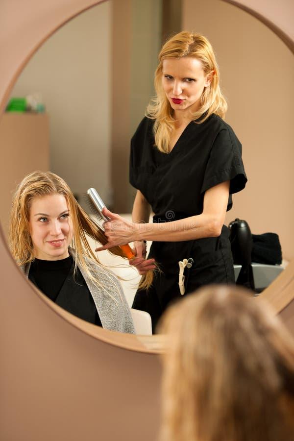 Yrkesmässig hårstylist på arbete - frisör som gör frisyren royaltyfri foto