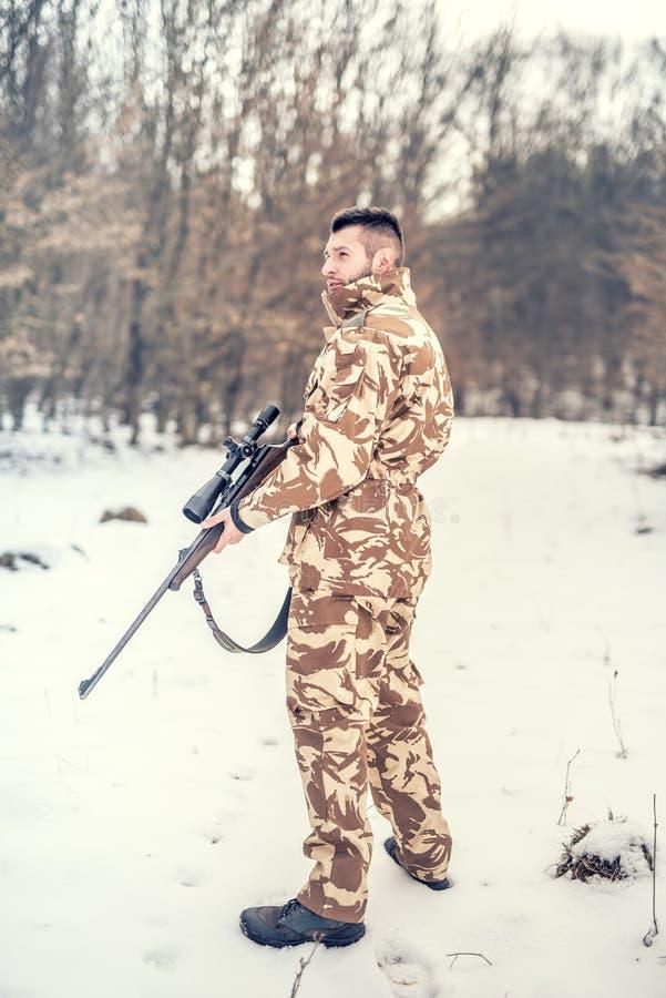 Yrkesmässig jägare som söker efter rovet under vintersäsong Krig-, jakt- eller skyddsbegrepp arkivfoto