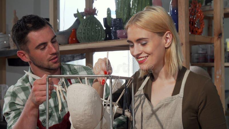 Yrkesmässig keramiker som hjälper hans kvinnliga student på seminariet royaltyfri fotografi