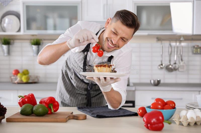Yrkesmässig kock som framlägger den läckra maträtten fotografering för bildbyråer