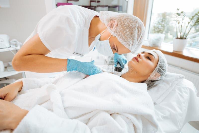 Yrkesmässig kompetent kvinnlig hudspecialist som använder en dermoscope royaltyfri bild