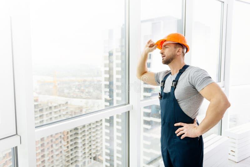Yrkesmässig konstruktionstekniker som står det near fönstret royaltyfri foto