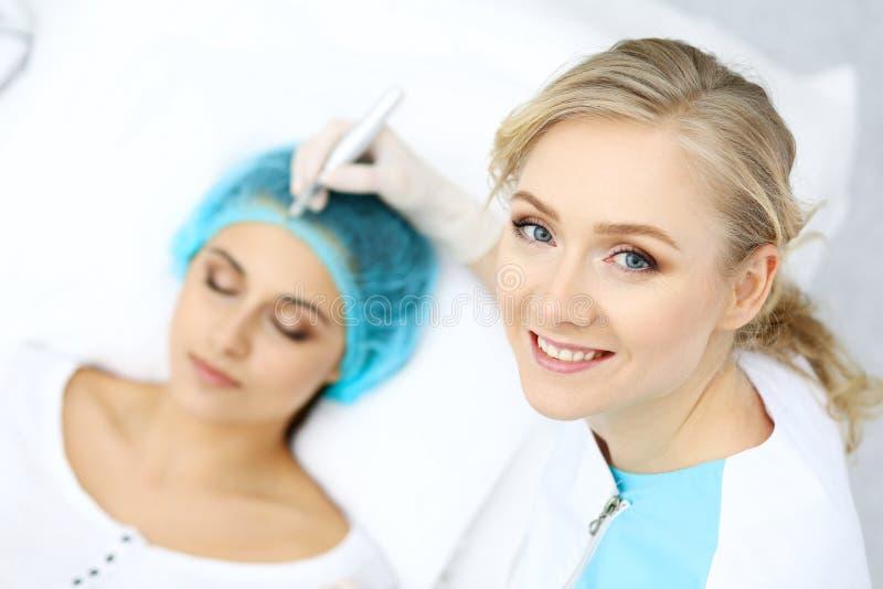 Yrkesmässig kosmetolog som gör ögonbryntatueringen på kvinnaframsidan Permanent krönmakeup i skönhetsalongen, closeup Fokusnolla royaltyfri bild
