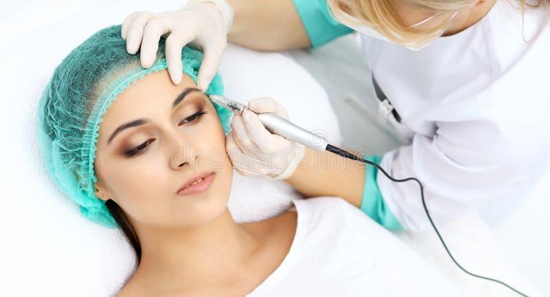 Yrkesmässig kosmetolog som gör ögonbryntatueringen på kvinnaframsidan Permanent krönmakeup i skönhetsalongen, closeup Cosmetolog fotografering för bildbyråer