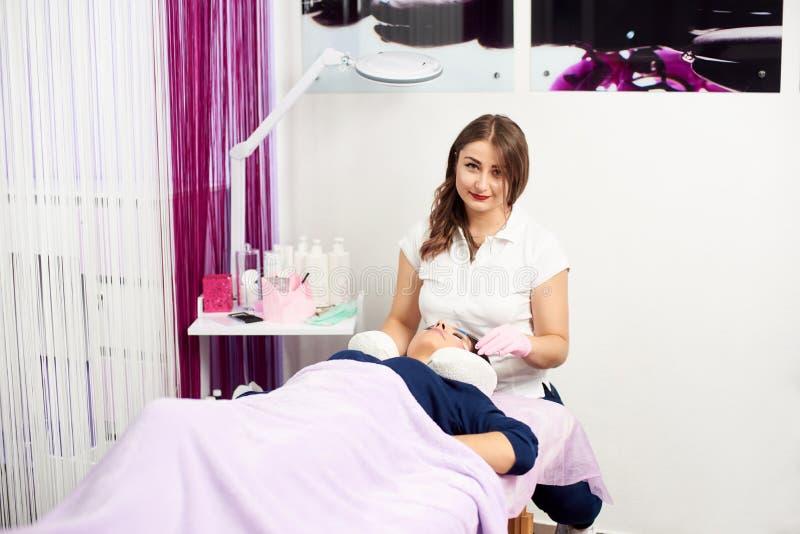 Yrkesmässig kosmetolog som genomgår ögonfransförlängningstillvägagångssätt i modern skönhetsalong royaltyfri fotografi