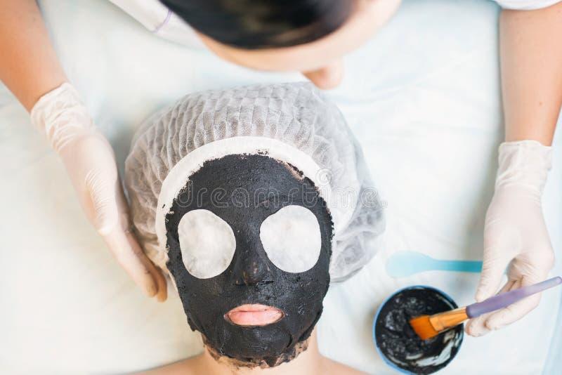 Yrkesmässig kvinna, cosmetologist i brunnsortsalongen som applicerar gyttjaframsidamaskeringen royaltyfri foto