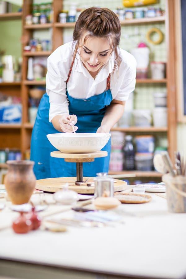 Yrkesmässig kvinnlig Ceramist i förkläde som glasar den keramiska bunken arkivfoto