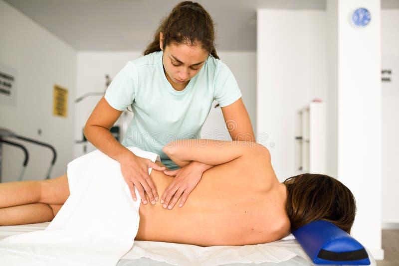 Yrkesmässig kvinnlig fysioterapeut som ger lumbal skuldramassa arkivbild