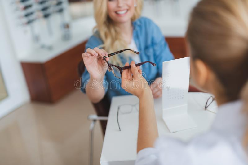 Yrkesmässig kvinnlig optiker som passerar exponeringsglas till hennes patient fotografering för bildbyråer