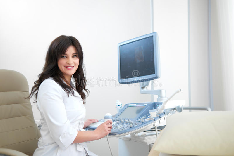 Yrkesmässig kvinnlig sjuksköterska som använder ultraljudutrustning royaltyfri bild