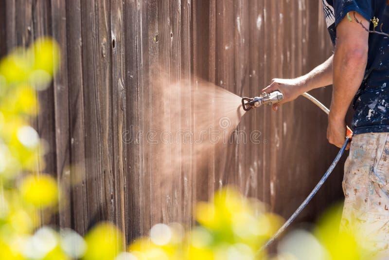 Yrkesmässig målare Spraying Yard Fence med fläck fotografering för bildbyråer