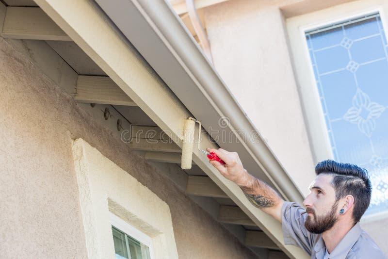 Yrkesmässig målare Using Small Roller som målar husfascian arkivfoto