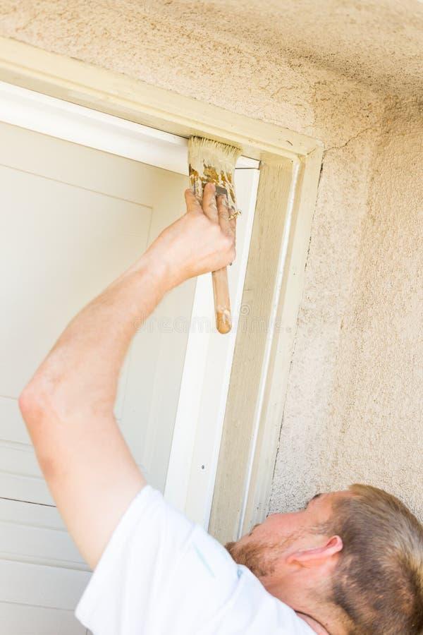 Yrkesmässig målareCutting In With borste som målar garagedörren arkivfoto