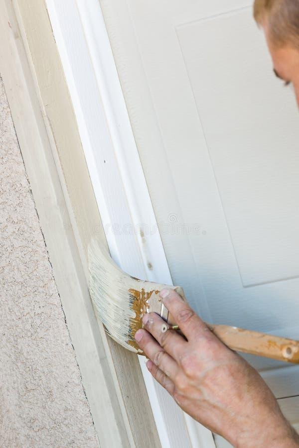 Yrkesmässig målareCutting In With borste som målar garagedörren royaltyfria foton