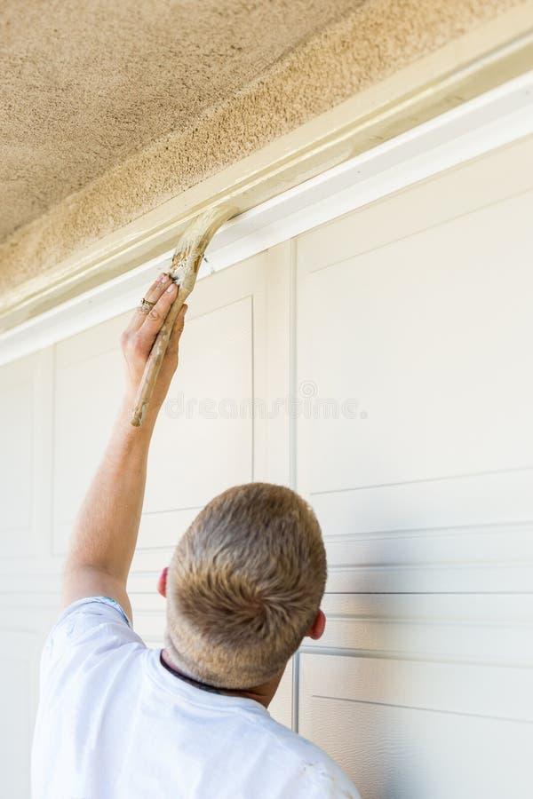 Yrkesmässig målareCutting In With borste som målar garagedörren royaltyfri fotografi