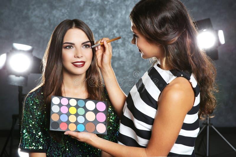 Yrkesmässig makeupkonstnär som arbetar med den härliga unga kvinnan arkivbilder
