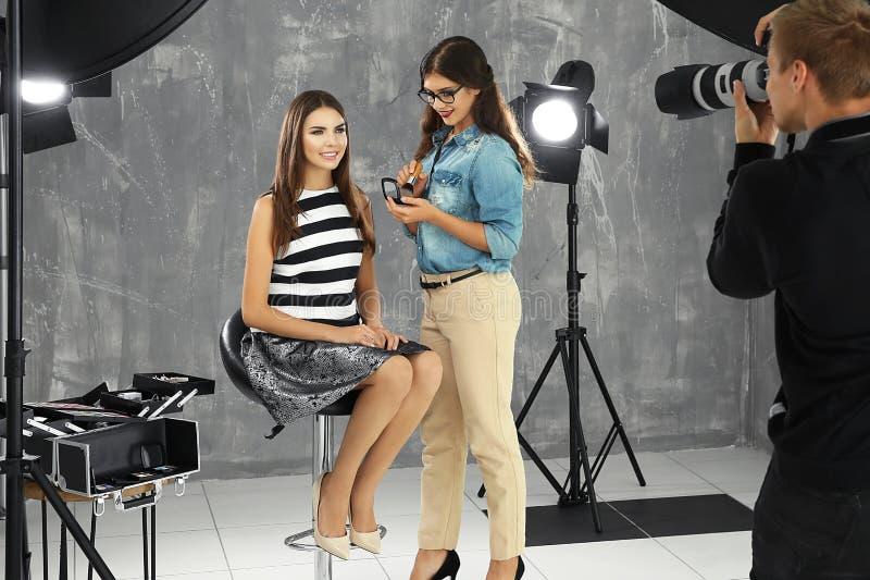 Yrkesmässig makeupkonstnär som arbetar med den unga kvinnan på fotoskytte royaltyfria foton