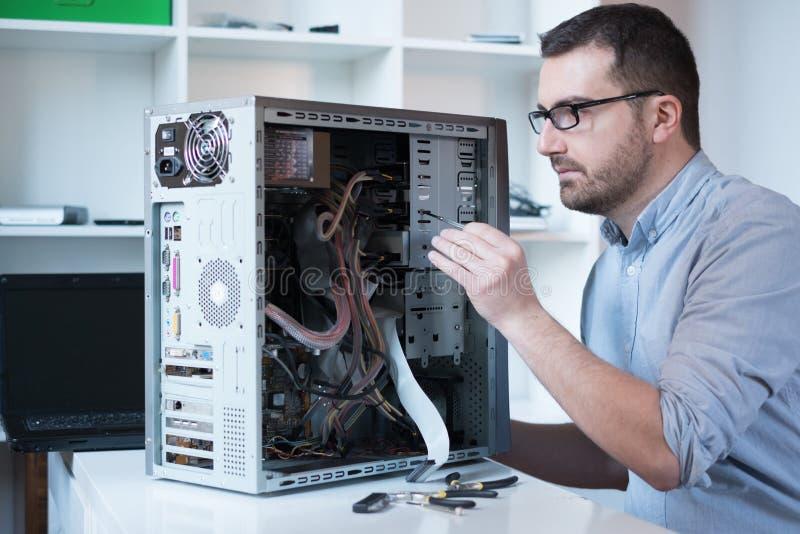 Yrkesmässig man som reparerar datoren royaltyfria bilder