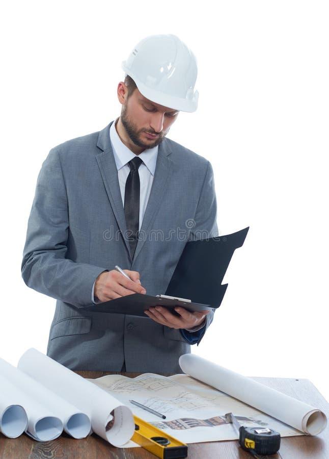 Yrkesmässig manlig constructionisthandstil på hans skrivplatta royaltyfri bild