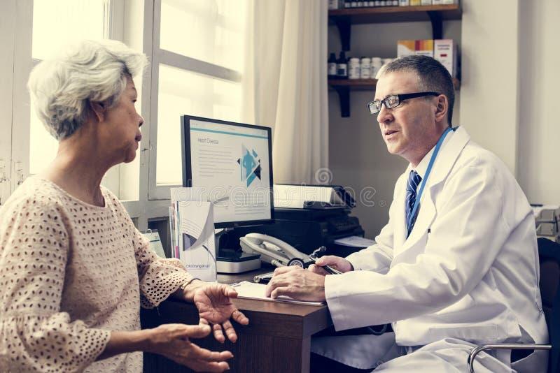 Yrkesmässig manlig doktor i likformig som talar med den höga patienten royaltyfria bilder