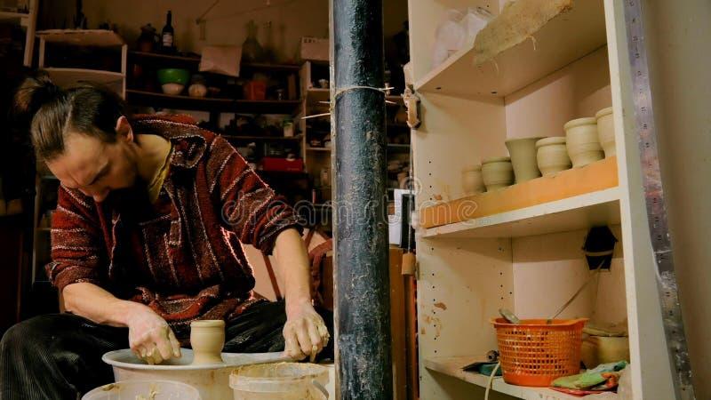 Yrkesmässig manlig keramiker som arbetar i seminariet, studio fotografering för bildbyråer