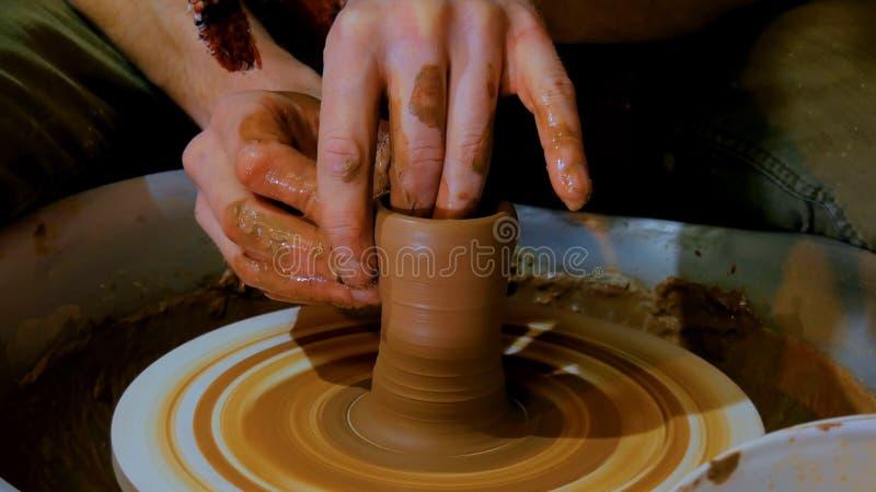 Yrkesmässig manlig keramiker som arbetar med lera på hjulet för keramiker` s royaltyfria bilder