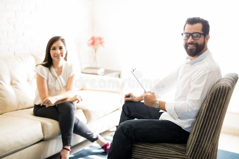 Yrkesmässig manlig psykolog med den kvinnliga klienten royaltyfri bild