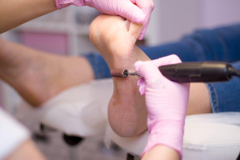 Yrkesmässig maskinvarupedikyr genom att använda rosa handskar och den elektriska apparatmaskinen Patient på det medicinska pediky arkivbild