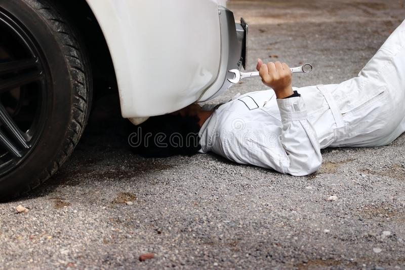 Yrkesmässig mekaniker i den vita likformign som ner ligger och fixar under bilen Service för auto reparation royaltyfri bild