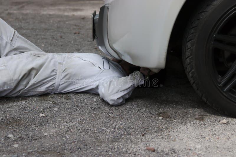 Yrkesmässig mekanikerman i den vita likformign som ner ligger och reparerar under bilen Bilunderhållsbegrepp arkivfoton
