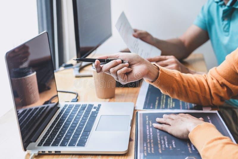 Yrkesmässig programmerare som två samarbetar och arbetar på webbplatsprojekt i en programvara som framkallar på den skrivbords- d arkivbilder
