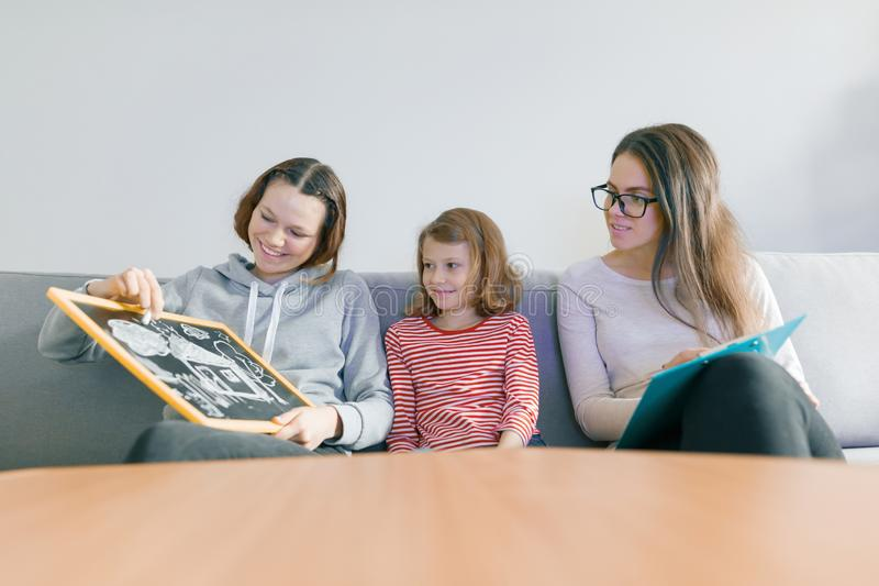 Yrkesmässig psykolog för barn som arbetar med familjen, två systrar i kontoret royaltyfri bild