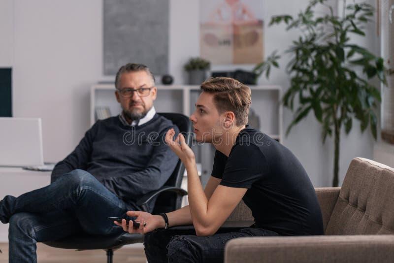 Yrkesmässig psykolog och tonåring som förklarar hans problem under terapi royaltyfria bilder