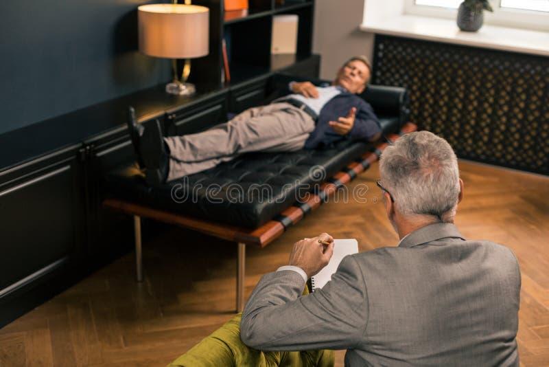 Yrkesmässig psykolog som sitter och lyssnar till en patient royaltyfri bild