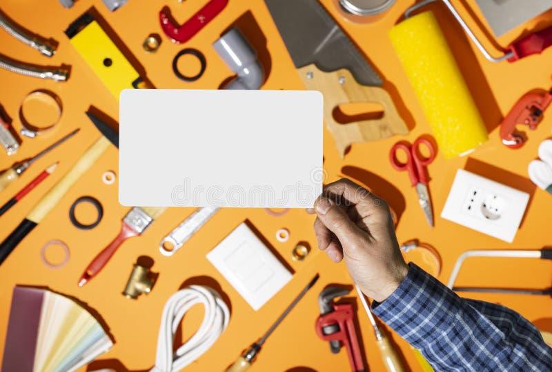 Yrkesmässig repairman som rymmer ett tomt kort och maskinvaruhjälpmedel royaltyfri bild