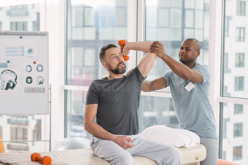 Yrkesmässig skicklig terapeut som arbetar med hans patient royaltyfri fotografi