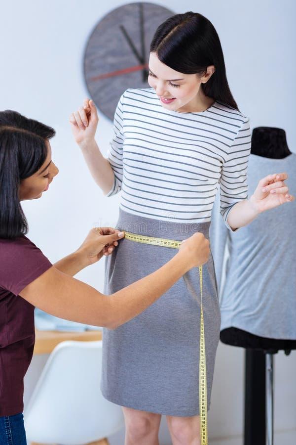 Yrkesmässig skräddare som mäter midjan av en klient och ser glad royaltyfri foto