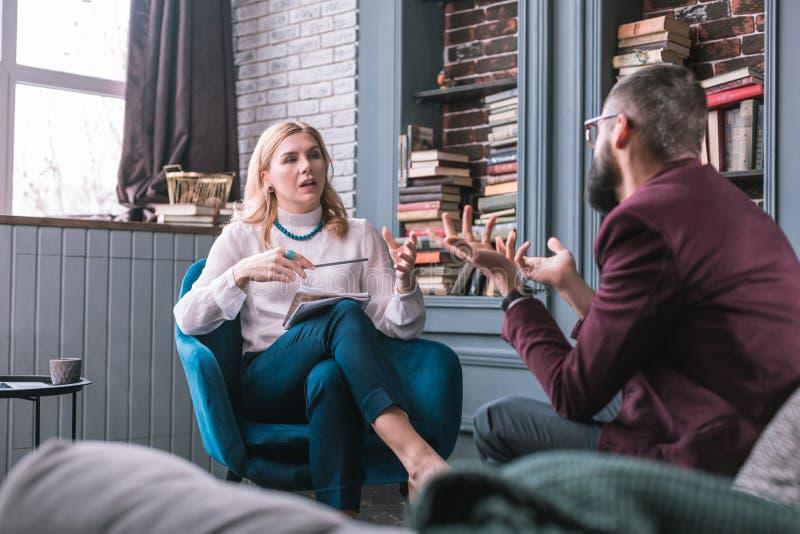 Yrkesmässig smart privat terapeut som talar till hennes konstanta klient arkivfoton