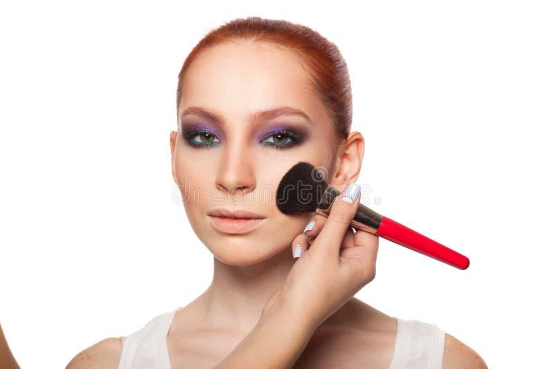 Yrkesmässig sminkkonstnär som gör glamour med röd hårmodellmakeup Isolerad bakgrund royaltyfria foton