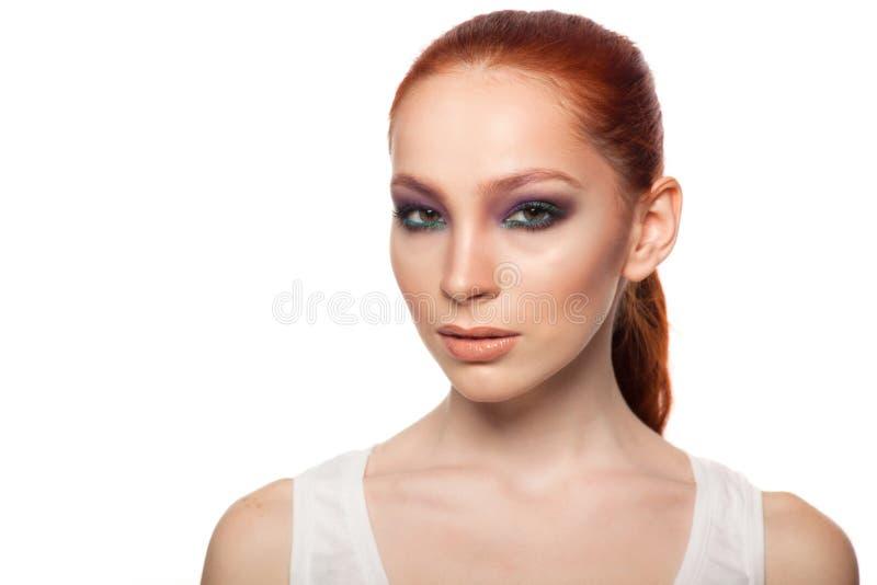 Yrkesmässig sminkkonstnär som gör glamour med röd hårmodellmakeup Isolerad bakgrund arkivbild
