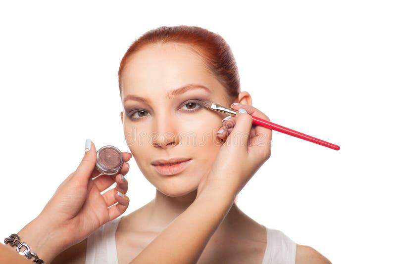 Yrkesmässig sminkkonstnär som gör glamour med röd hårmodellmakeup Isolerad bakgrund arkivbilder