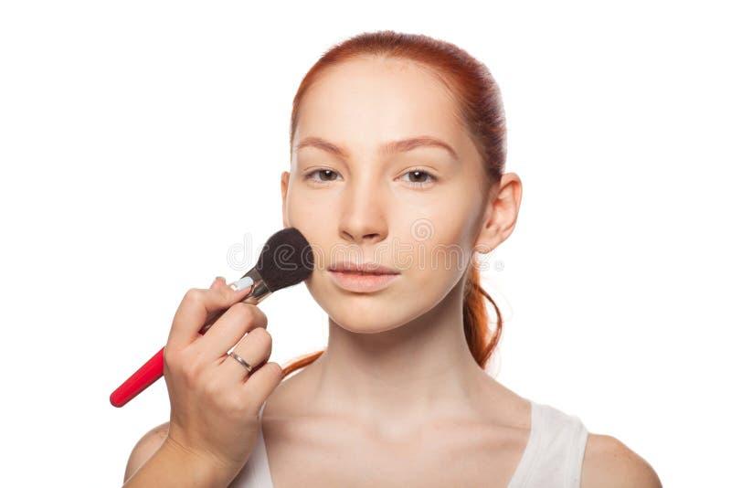 Yrkesmässig sminkkonstnär som gör glamour med röd hårmodellmakeup Isolerad bakgrund fotografering för bildbyråer