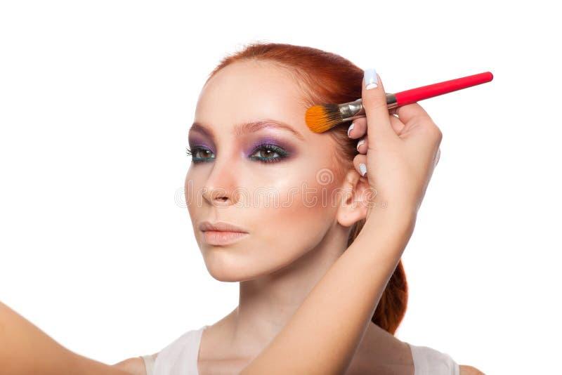 Yrkesmässig sminkkonstnär som gör glamour med rött arkivfoto