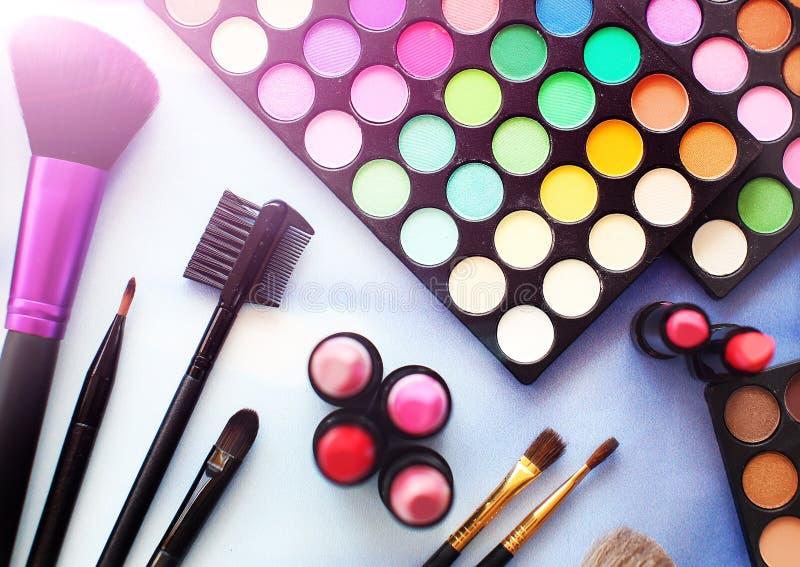Yrkesmässig sminkuppsättning: ögonskuggapalett, läppstift, sminkborstar Film- och signalljuseffekt Bästa sikt som är flatlay royaltyfri fotografi