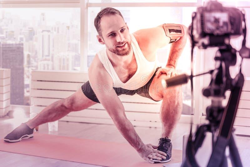 Yrkesmässig stilig idrottsman som framme gör övningar av kameran arkivbilder