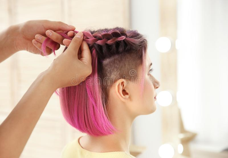 Yrkesmässig stylist som flätar hår för färg för kvinna` s arkivfoton