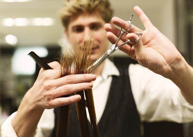Yrkesmässig stylistbrämkluvna hårtoppar på kvinnligt hår på salongen arkivfoto