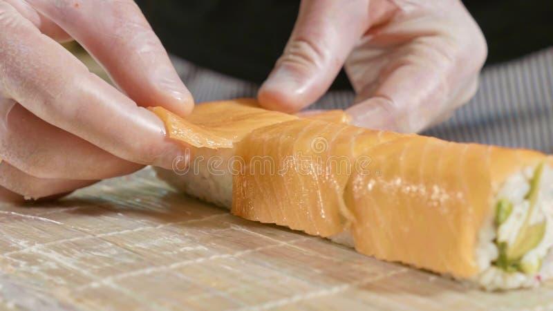 Yrkesmässig sushikock som förbereder rulle på kommersiellt kök, närbild royaltyfri fotografi
