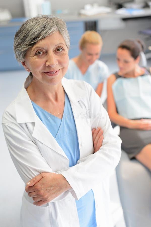 Yrkesmässig tandläkarekvinnapatient på tand- kirurgi arkivfoto